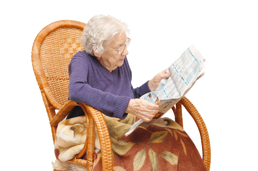 Grandmother reads the newspaper in an armchair